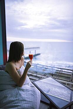 Woman sitting on bed with cocktail in hotel and observing sunrise over sea