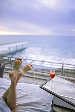 Woman's feet and cocktail in hotel room with view on sea at sunrise