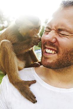 Portrait of man holding monkey, Thailand