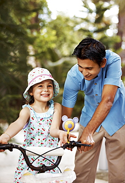 Man assisting girl (6-7) riding bicycle