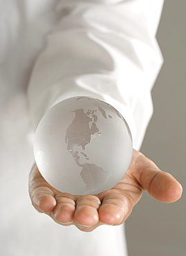 Glass globe held in outstretched hand