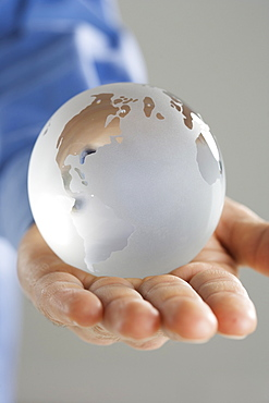 Closeup of glass globe in palm