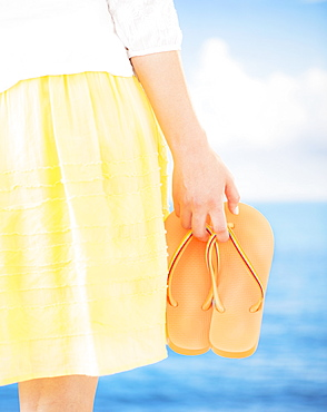 Studio Shot Mid section of woman holding flip-flops, rear view
