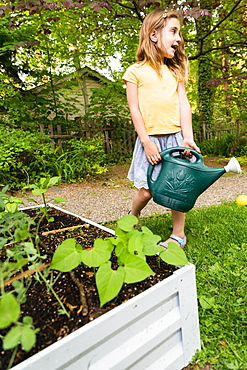 Girl holding watering can in garden
