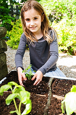 Smiling girl planting seedling