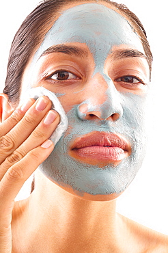 Close-up of woman removing blue facial mask