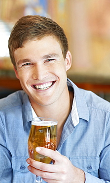 Portrait of man holding glass of beer