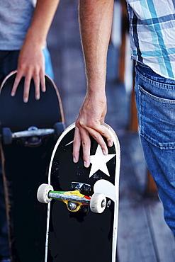 Close-up of men holding skateboardes