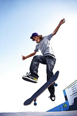 Skater performing jump in skateboard park