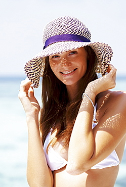 Portrait of young woman in bikini and straw hat