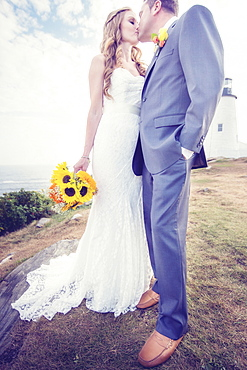 Portrait of married couple kissing, lighthouse in background, USA, Maine, Bristol