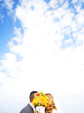 Portrait of married couple kissing behind bouquet