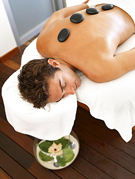 Man getting lastone therapy in spa