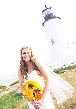 Portrait of smiling bride holding sunflower bouquet, lighthouse in background, USA, Maine, Bristol