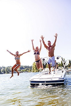 Young people jumping to lake from motorboat, USA, Washington, Bellingham
