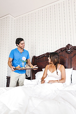 Man bringing woman breakfast to bed in hotel room