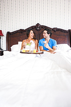 Young couple eating breakfast in bed in hotel room