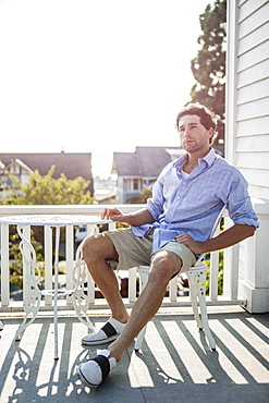 Portrait of young man relaxing on balcony, USA, Washington, Everett
