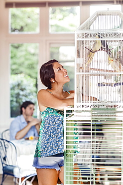 Woman standing by bird cage, man in background