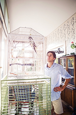 Portrait of young man standing by bird cage and looking at parrot