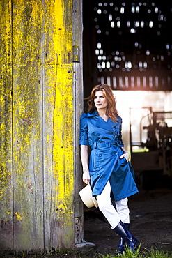 USA, Washington, Skagit Valley, Woman leaning on barn gate, USA, Washington, Skagit Valley