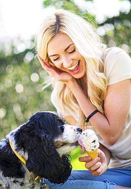 Portrait of teenage girl (16-17) with dog licking ice cream