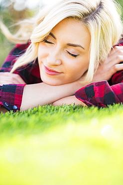 Teenage girl (16-17) sleeping on grass