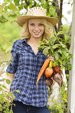 Portrait of young woman holding fresh vegetables in garden