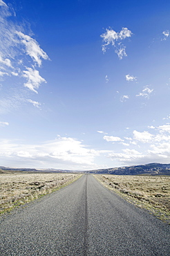 Road going through desolate landscape, Wyoming, USA