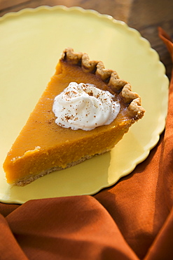 Slice of homemade pumpkin pie on plate