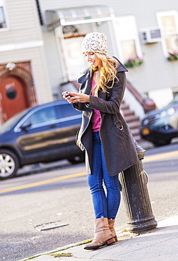 Portrait of woman standing by fire hydrant and text messaging, USA, New York City, Brooklyn, Williamsburg