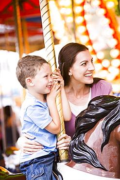 Mother and son (4-5) on carousel in amusement park, USA, Utah, Salt Lake City