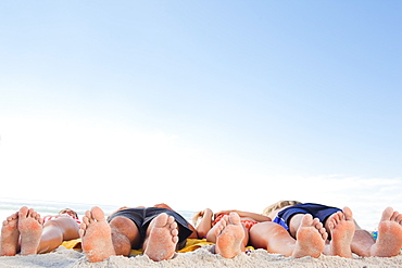Two couples lying on their backs soaking up the sun