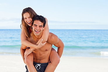 Portrait of an attractive man carrying on his back his girlfriend