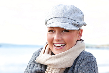 Pretty woman with scarf and hat standing on the beach
