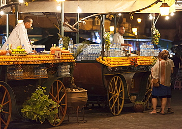 Orange juice sellers and tourists in the Djemaa El Fna at sunset, Marrakech, Morocco, North Africa, Africa