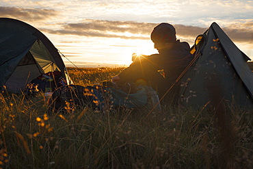 A camper sits in the evening sun, Picws Du, Black Mountain, Brecon Beacons National Park, Wales, United Kingdom, Europe