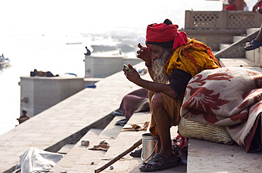 A Saddhu applies a tikka to his forehead while sitting at a ghat on the banks of the River Ganges, Varanasi, India