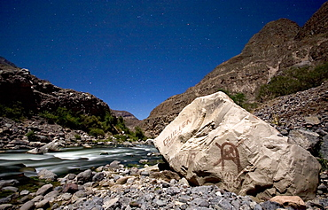 The river running through the bottom of the Cotahuasi Valley, Peru. At places this is the deepest canyon in the world. Local political slogans and symbols have been daubed on the rock. Lit by moonlight.