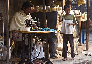 A tailor mends an article of clothing while a young boy looks on. Kali Ghat, Calcutta, India.