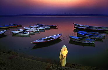 Devotee woman praying at the ghat ( river bank ) at dawn. Varanasi , India