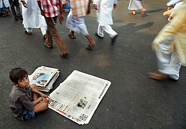 A little boy selling newspapers  on the street of Kolkata, India