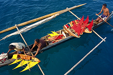 Local men transport model boats by canoe to market, Nosy Be Island, Madagascar, Africa