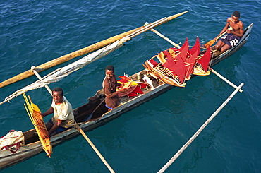 Men in outrigger canoes selling model boats with red sails, Nosy Be, Madagascar, Africa