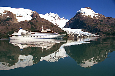 Reflections of the Seabourn Pride cruise ship, mountains and glacier in Chilean Fjordland, Magallanes, Chile, South America
