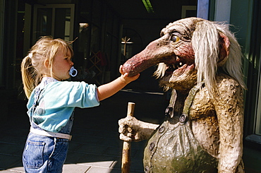 Young girl with dummy in her mouth, touching troll statue with long nose, Norway, Scandinavia, Europe