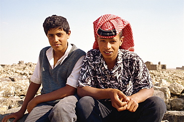 Portrait of two young local guides, one wearing traditional headcloth, at the ruins at Umm al Jimal, Jordan, Middle East