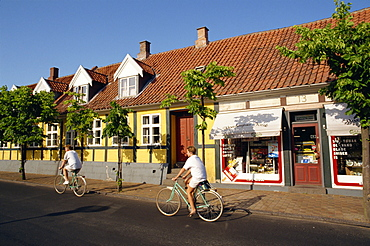 Cyclists pass small shop in Ronne, Bornholm Island, Denmark, Scandinavia, Europe