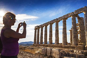 Tourist taking photo of Temple of Poseidon, Cape Sounion, near Athens, greece, Europe