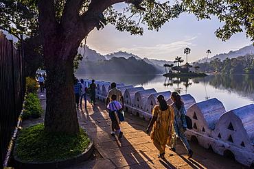 Sri Lankan people walking at Kandy Lake at sunrise, Kandy, Central Province, Sri Lanka, Asia